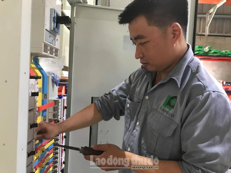 Ninh đang hoàn thiện tủ điện trong xưởng sản xuất của công ty.