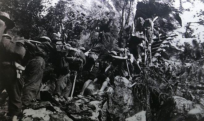 Ngày 19/5/1959, Binh đoàn Trường Sơn (Đoàn 559) thành lập, đánh dấu sự khởi đầu của tuyến đường Trường Sơn. Mạng lưới giao thông quân sự này chạy dọc dãy Trường Sơn, từ miền Bắc qua miền Trung, hạ Lào và Campuchia để chi viện cho Quân Giải phóng miền Nam và Quân đội Nhân dân Việt Nam. Vào những năm đầu, việc vận chuyển hàng chi viện được thực hiện bằng hình thức đi bộ, gùi thồ. Trong ảnh là các chiến sĩ của trung đoàn 70 - đơn vị đầu tiên của bộ đội Trường Sơn - đang thồ hàng trên tuyến Tây Trường Sơn tháng 9/1961.