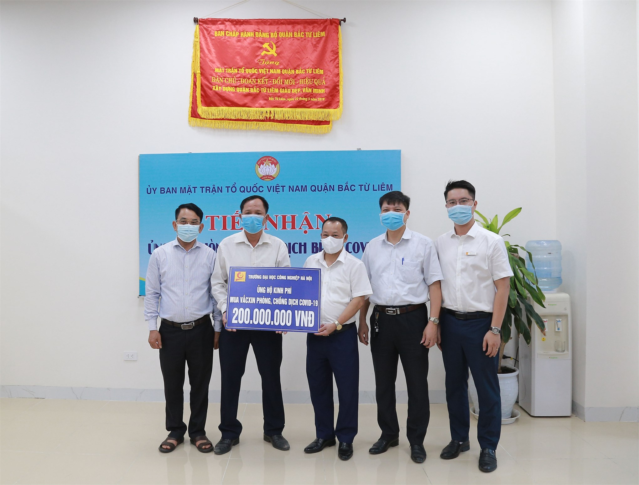 Dr. Nguyen Anh Tuan - Vice-Rector (in the center) symbolically donated to the Vietnam Fatherland Front Committee of Bac Tu Liem district. According to Dr. Nguyen Anh Tuan, in recent days, the situation of the COVID-19 pandemic has been complicated across the country. HaUI wishes to share with the community, to realize the